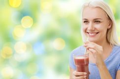 Lächelnder trinkender Saft oder Erschütterung der Frau lizenzfreie stockbilder