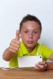 Lächelnder Tweenjunge, der seinen Smartphone verwendet Stockbilder