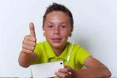 Lächelnder Tweenjunge, der seinen Smartphone verwendet Lizenzfreie Stockfotografie