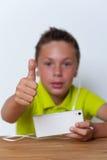 Lächelnder Tweenjunge, der seinen Smartphone verwendet Lizenzfreies Stockbild