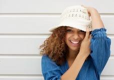 Lächelnder und tragender Hut der attraktiven jungen Frau auf weißem Hintergrund Stockfotos