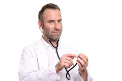 Lächelnder unrasierter männlicher Doktor, der ein Stethoskop prüft Lizenzfreie Stockfotografie