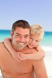Lächelnder Vater, der Sohn ein Doppelpol hat stockfoto