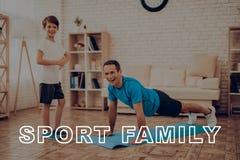 Lächelnder Vater Is Doing Push Ups Sportfamilie stockbilder