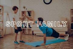 Lächelnder Vater Is Doing Push Ups Sportfamilie lizenzfreie stockfotografie