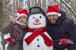 Lächelnder Vater und daugter mit einem Schneemann Stockbild