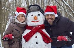 Lächelnder Vater und daugter mit einem Schneemann Lizenzfreie Stockbilder