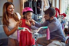 L?chelnder Vater und kaufendes neues Fahrrad und Sturzhelme der Mutter f?r wenig M?dchen im Fahrradgesch?ft stockbild
