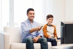 Lächelnder Vater und Sohn, die zu Hause fernsehen stockbild