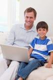 Lächelnder Vater und Sohn, die zusammen das Internet surfen Stockbilder