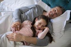 Lächelnder Vater und Tochter, die auf Bett im Schlafzimmer liegen stockfoto
