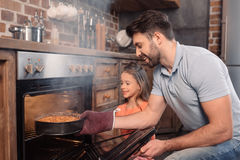 Lächelnder Vater und Tochter, die Kuchen vom Ofen nehmen stockfotografie