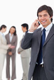 Lächelnder Verkäufer auf Mobiltelefon mit Team hinter ihm Stockbilder
