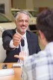 Lächelnder Verkäufer, der einem Kunden Autoschlüssel gibt Stockbild