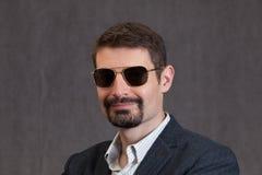 Lächelnder Vierzigermann mit Sonnenbrille, Spitzbartbart und dem Schnurrbart Lizenzfreie Stockfotografie