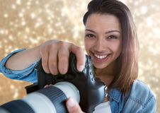lächelnder Vordergrund des Fotografen mit Goldlichtern hinten Stockfotos