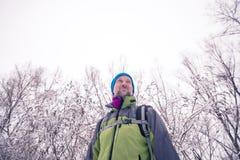 Lächelnder Wanderer ist im Winterwald entspannend Stockfotos