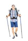 Lächelnder Wanderer mit dem Rucksack- und Wanderstockgehen Stockfotos