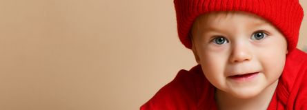 Lächelnder warmer Kleidungshut des kleines Kinderbabys auf beige Atelieraufnahme lizenzfreies stockbild