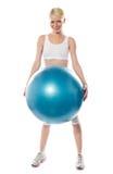 Lächelnder weiblicher Athlet, der eine große blaue Kugel anhält Lizenzfreie Stockbilder