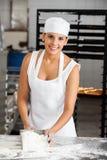Lächelnder weiblicher Bäcker Holding Flour Scoop bei Tisch Lizenzfreies Stockfoto