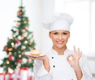 Lächelnder weiblicher Chef mit kleinem Kuchen auf Platte lizenzfreie stockfotos