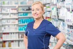 Lächelnder weiblicher Chemiker Standing In Pharmacy Stockfoto