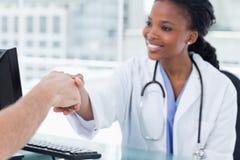 Lächelnder weiblicher Doktor, der eine Hand rüttelt Stockfotografie