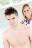 Lächelnder weiblicher Doktor, der ihren männlichen Patienten klingt Lizenzfreie Stockbilder