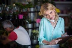 Lächelnder weiblicher Florist, der eine Bestellung am Telefon entgegennimmt stockfoto