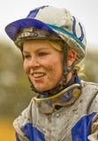 Lächelnder weiblicher Jockey mit einem schlammigen Gesicht im Regen Stockbild