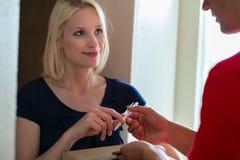 Lächelnder weiblicher Kunde, der Stift vom Lieferer nimmt lizenzfreie stockbilder
