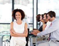 Lächelnder weiblicher Manager, der in einem Kundenkontaktcenter arbeitet stockbild