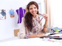 Lächelnder weiblicher Modedesigner, der im Büro sitzt stockbild