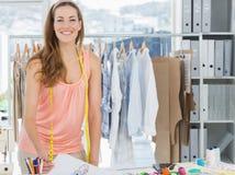 Lächelnder weiblicher Modedesigner, der im Studio arbeitet Stockbilder