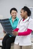 Lächelnder weiblicher Patient mit Doktor Holding X-ray In Hospital Lizenzfreie Stockbilder
