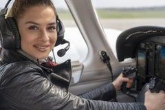 Lächelnder weiblicher Pilot im Cockpit eines Flugzeuges lizenzfreies stockfoto
