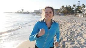 Lächelnder weiblicher Rüttler bei Sonnenuntergang auf dem Strand stock video footage