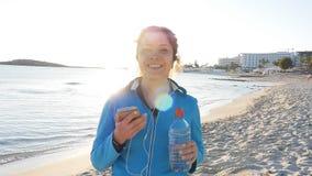 Lächelnder weiblicher Rüttler bei Sonnenuntergang auf dem Strand stock footage