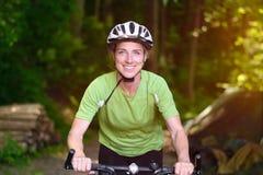 Lächelnder weiblicher Radfahrer, der grünes Hemd trägt lizenzfreies stockfoto