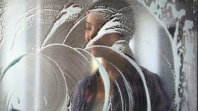Lächelnder weiblicher Reiniger, der die Glastür entfernt Staub und Schmutz, Haushaltung abwischt Stockfotos