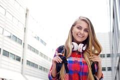 Lächelnder weiblicher Student mit Tasche und Kopfhörern Lizenzfreies Stockbild