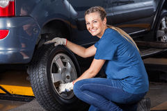 Lächelnder weiblicher Techniker Adjusting Car Tire Stockfoto