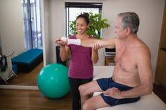 Lächelnder weiblicher Therapeut, der Hand des älteren männlichen Patienten hält Lizenzfreie Stockfotos