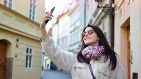 Lächelnder weiblicher Tourist, der das selfie unter Verwendung der Smartphoneaufstellung umgeben durch historische Architektur n stock video