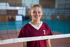 Lächelnder weiblicher Volleyballspieler, der hinter dem Netz steht Stockbilder
