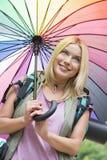 Lächelnder weiblicher Wanderer, der Regenschirm hält Stockfoto