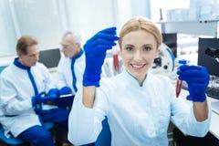 Lächelnder Wissenschaftler, der das Reagenzgläser und Tragen einer Uniform hält Lizenzfreies Stockfoto