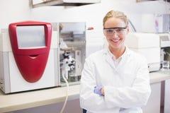 Lächelnder Wissenschaftler, der die Kameraarme gekreuzt betrachtet stockfotos
