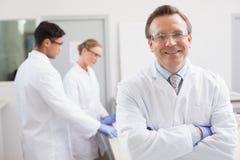 Lächelnder Wissenschaftler, der Kamera während Kollegen hinten arbeiten betrachtet stockfotografie